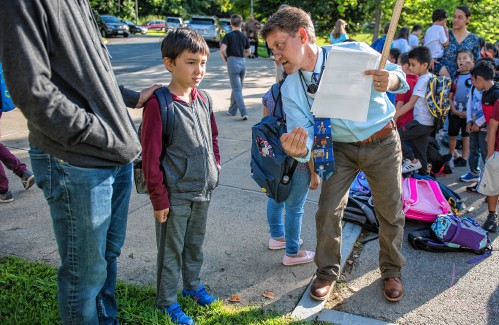Crocker Farm School second grade teacher Jeff Lefebvre welcomes his student Henry Kwak to the line outside the Amherst elementary school on the first day of classes on Wednesday.